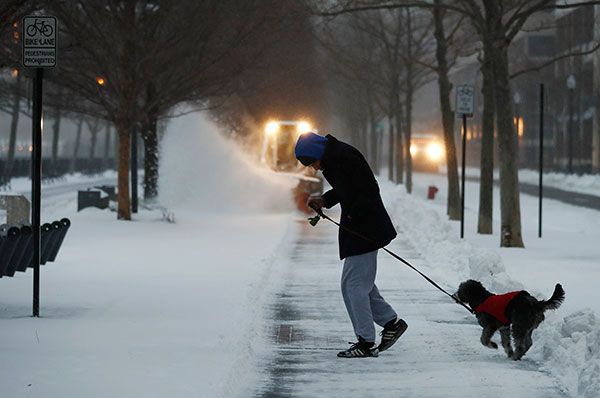 """<div class=""""meta image-caption""""><div class=""""origin-logo origin-image none""""><span>none</span></div><span class=""""caption-text"""">A man hunches in strong winds while walking his dog during a snowstorm, Tuesday, March 14, 2017, in Hoboken, N.J. (Julio Cortez/AP Photo)</span></div>"""