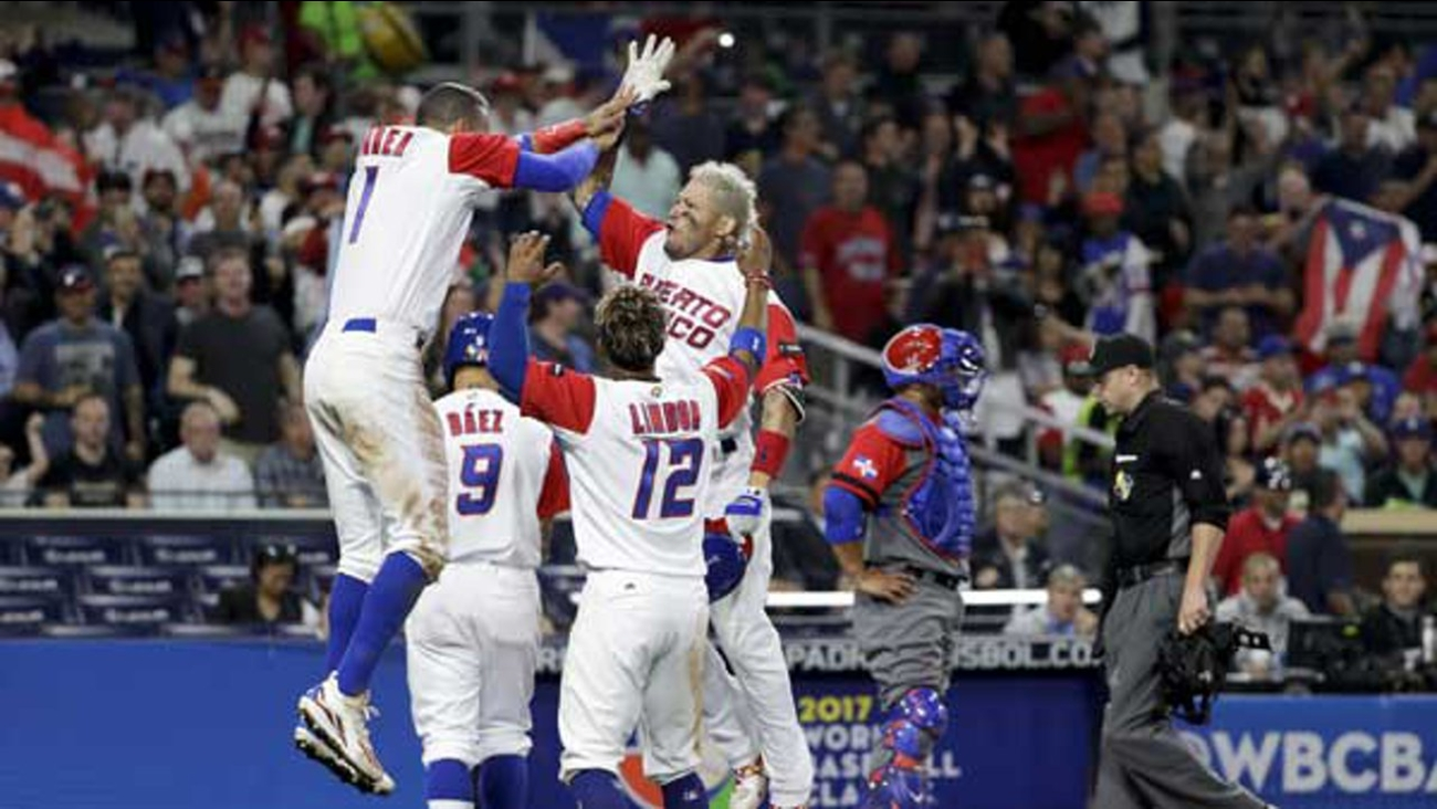Puerto Rico's Yadier Molina, second from right, reacts with teammates after hitting a home run during the sixth inning of a second-round World Baseball Classic game against the Dominican Republic.