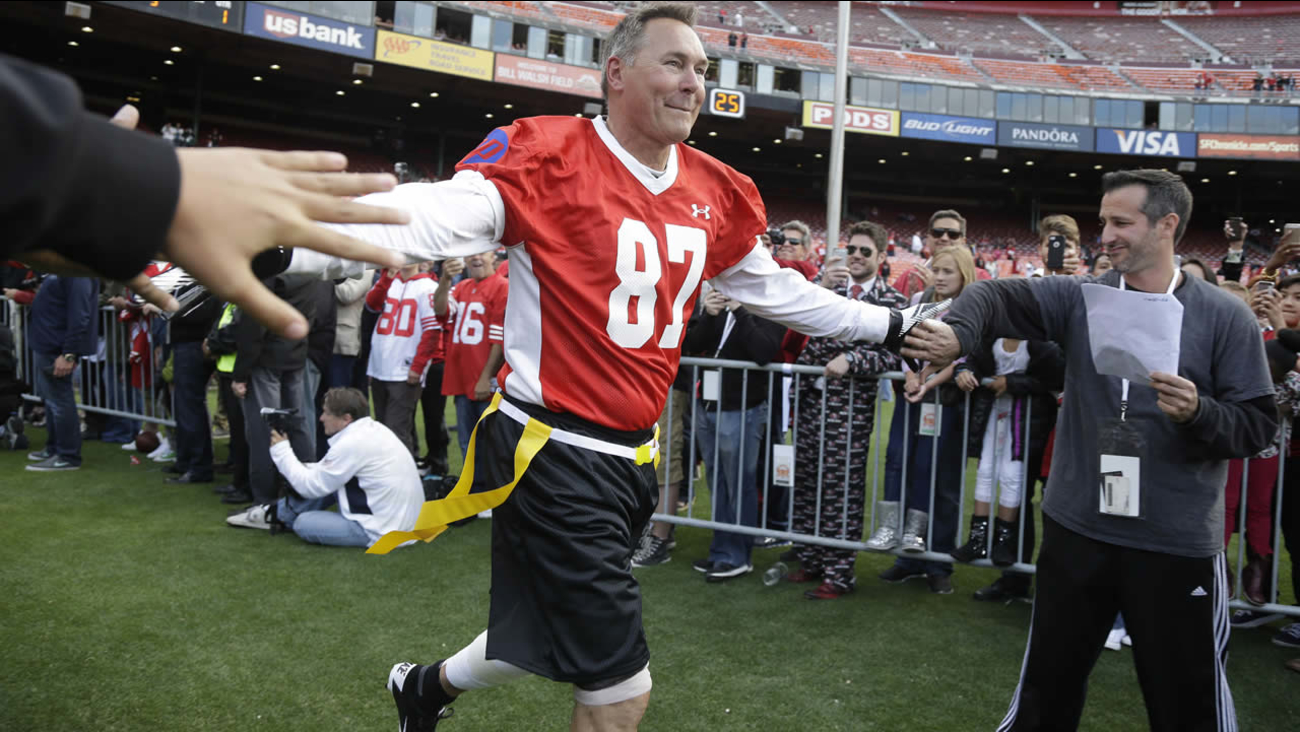 "Former San Francisco 49ers' Dwight Clark runs onto the field before the start of the ""Legends of Candlestick"" flag football game July 12, 2014, in San Francisco. (AP Photo)"