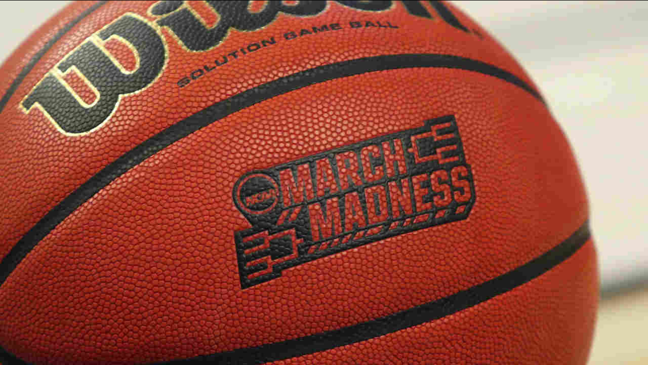 A closeup view of an official game ball with the March Madness logo.
