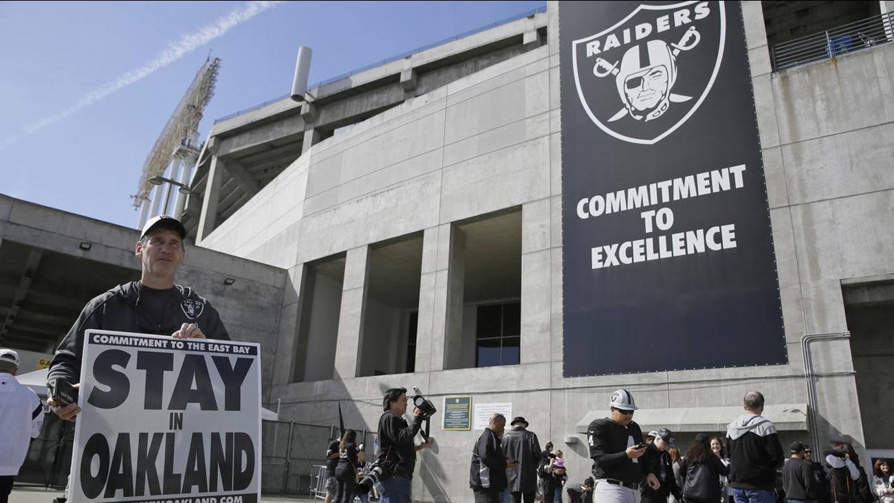 John P. Kelleher holds up a sign outside the Oakland Coliseum before the start of a rally to keep the Raiders from moving, Saturday, March 25, 2017, in Oakland, Calif. (AP Photo)