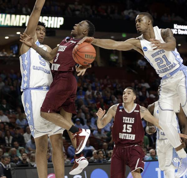 """<div class=""""meta image-caption""""><div class=""""origin-logo origin-image ap""""><span>AP</span></div><span class=""""caption-text"""">UNC's Seventh Woods (21) blocks a shot by Texas Southern's Demontrae Jefferson (3) as Tony Bradley (5) defends during the first half in a first-round NCAA Tournament game (AP Photo/Chuck Burton)</span></div>"""