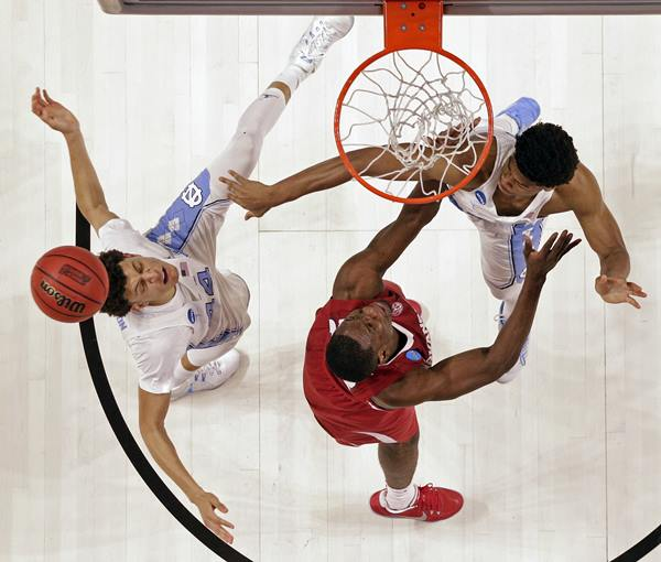 """<div class=""""meta image-caption""""><div class=""""origin-logo origin-image ap""""><span>AP</span></div><span class=""""caption-text"""">North Carolina's Justin Jackson, left, and Isaiah Hicks, right, battle Arkansas' Moses Kingsley, center for a rebound during the second half in a second-round game (AP Photo/Chuck Burton)</span></div>"""