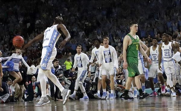 "<div class=""meta image-caption""><div class=""origin-logo origin-image ap""><span>AP</span></div><span class=""caption-text"">North Carolina's Theo Pinson (1) celebrates as Oregon's Payton Pritchard (3) walks off the court after the semifinals of the Final Four NCAA college basketball tournament (AP Photo/David J. Phillip)</span></div>"