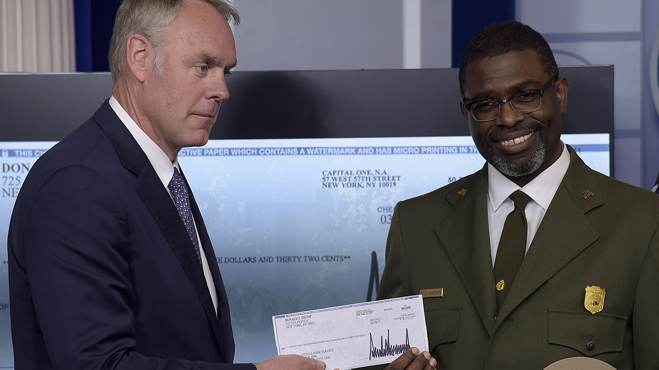Interior Secretary Ryan Zinke, left, and Harpers Ferry National Historic Park Superintendent Tyrone Brandyburg, hold up a check from President Trump's three-month salary.