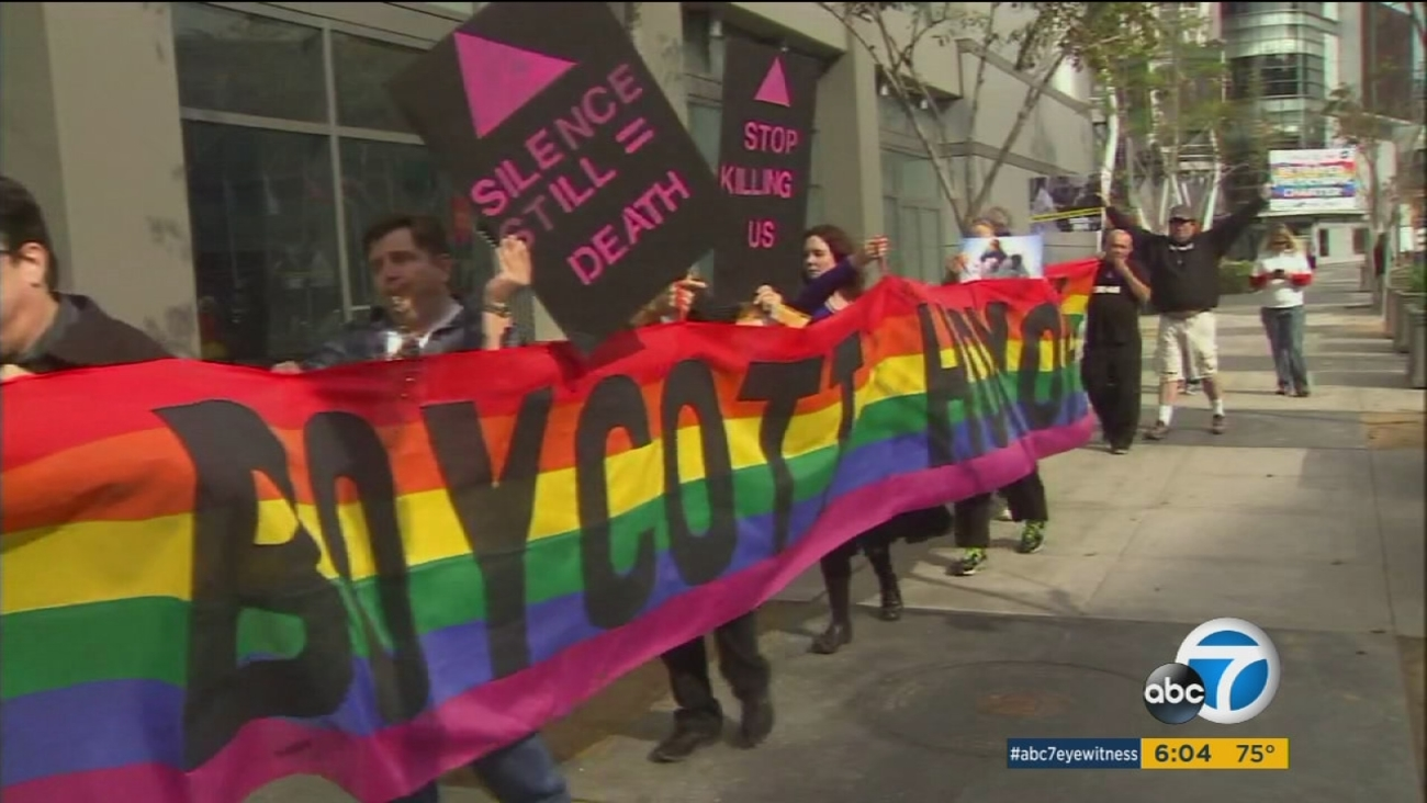 A group of protesters hold up LGBTQ signs and a banner in response to hate crimes committed against the sexual orientation group.