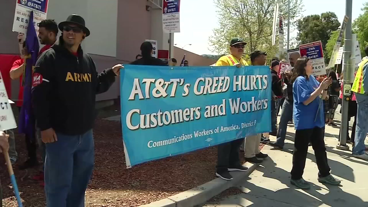 AT&T employees are seen holding signs in San Jose, Calif. on Sunday, April 9, 2017.