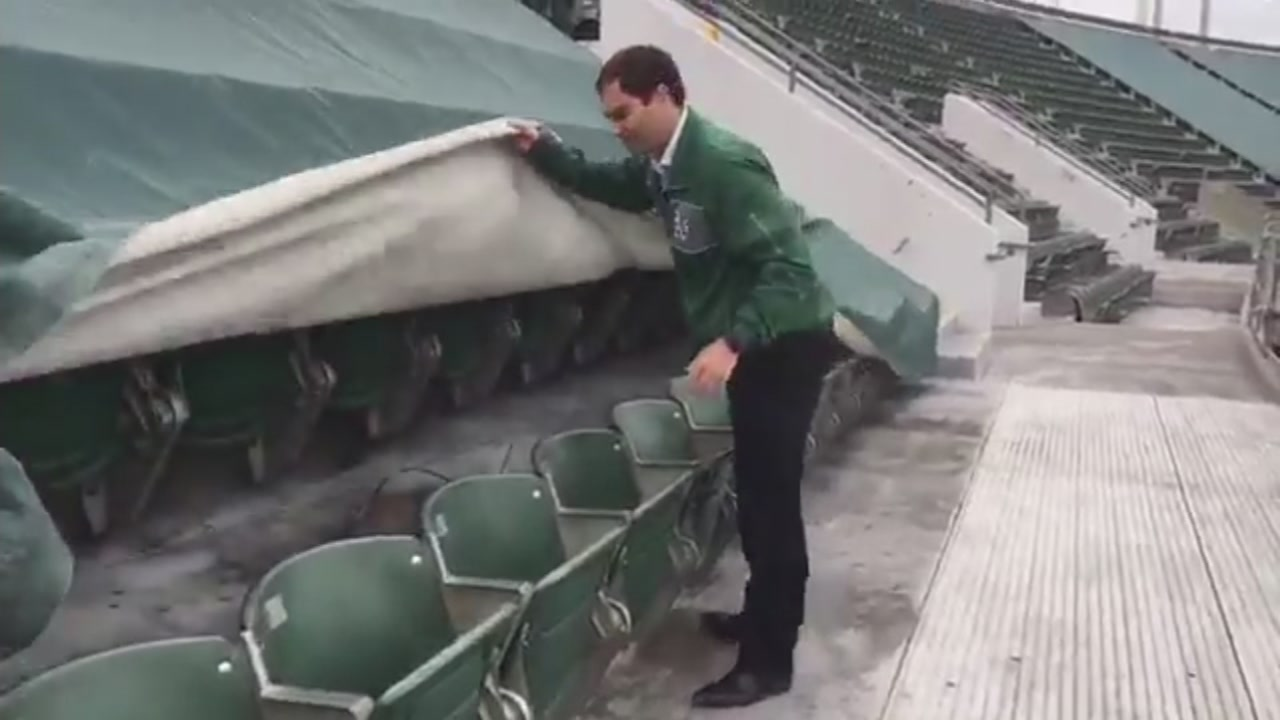 Oakland Athletics President Dave Kaval is seen pulling tarps down from the third deck of the Oakland Coliseum on Tuesday April 11, 2017.
