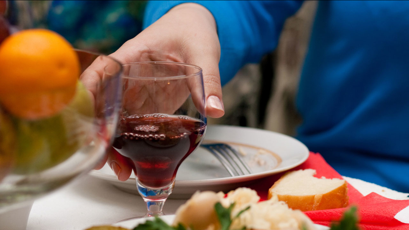A stock photo shows a women grabbing a glass of wine.