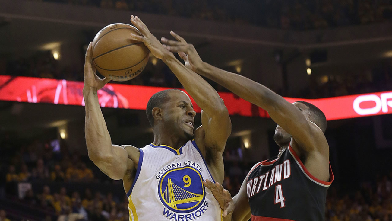 Warriors' Andre Iguodala passes the ball between Trail Blazers' Pat Connaughton during Game 1 of the NBA Playoffs in Oakland, Calif., Sunday, April 16, 2017. (AP Photo/Jeff Chiu)