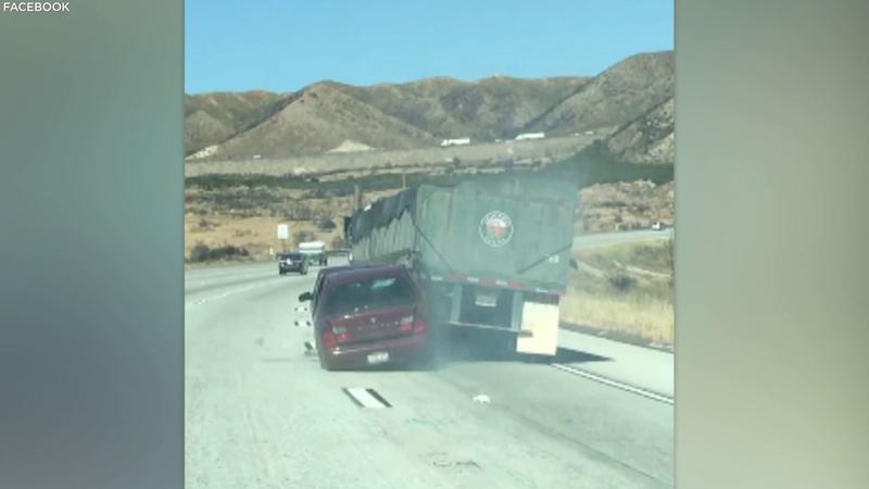 VIDEO: Car, lodged under semitruck, dragged along 15 Freeway