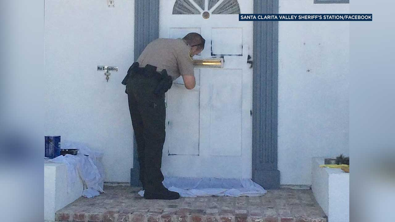 Deputy Scott Peterson is seen painting over graffiti on a door at the home of a Saugus widow in this photo posted to the Santa Clarita Valley Sheriff's Station's Facebook page.