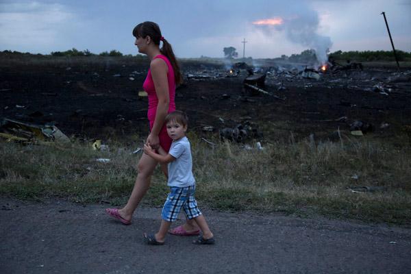 "<div class=""meta image-caption""><div class=""origin-logo origin-image ""><span></span></div><span class=""caption-text"">A woman with a child walks past the crash site of a passenger plane near the village of Grabovo, Ukraine, Thursday, July 17, 2014. (AP Photo/Dmitry Lovetsky)</span></div>"