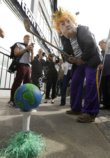 """<div class=""""meta image-caption""""><div class=""""origin-logo origin-image ap""""><span>AP</span></div><span class=""""caption-text"""">A protester pretends to golf with a prop during a protest across the street from the Intrepid, where the President is expected to attend a Commemorative Dinner. (AP Photo/Julio Cortez)</span></div>"""