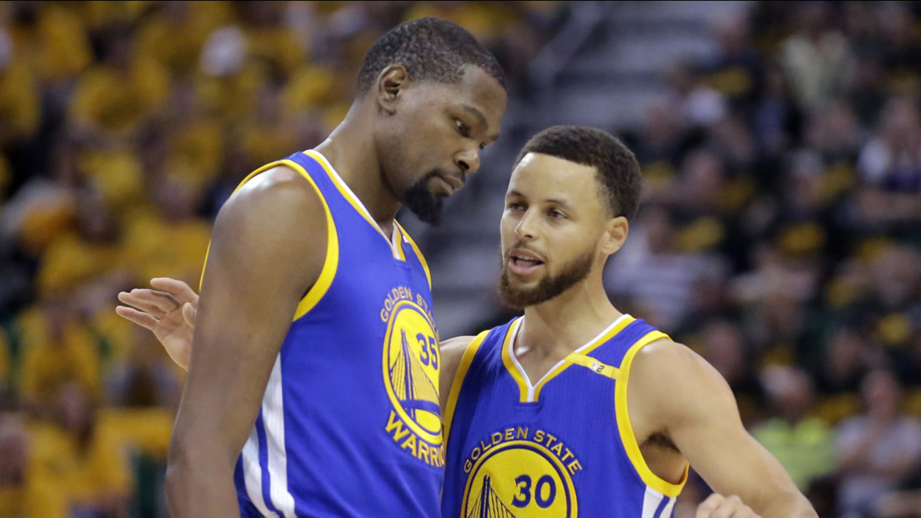 Golden State Warriors' Stephen Curry and Kevin Durant talk in the first half during Game 3 of an NBA playoff series in Salt Lake City, Utah.