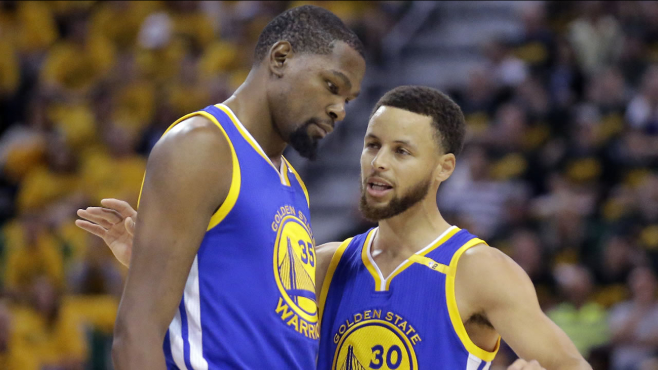 Warriors' Stephen Curry (30) and Kevin Durant (35) talk in the first half during Game 3 of the NBA basketball second-round playoff series against the Utah Jazz, Sat., May 6, 2017.