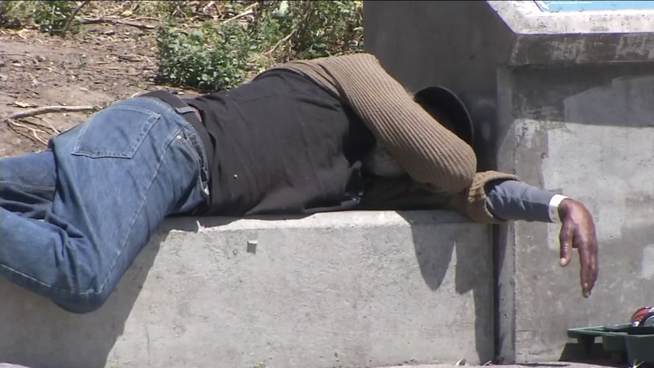 This undated image shows a homeless man sleeping on a bench in San Francisco.