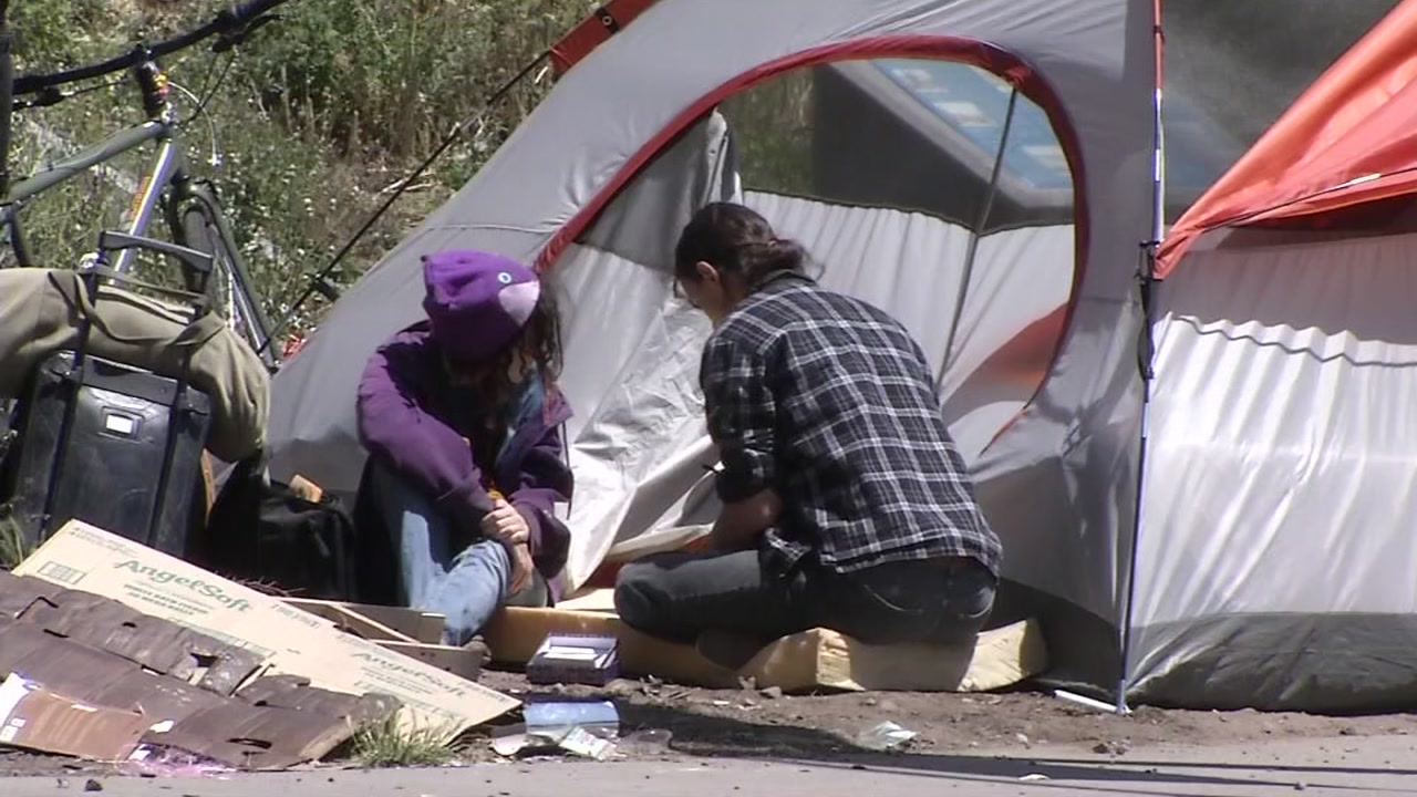 This undated image shows a homeless man and woman in front of a tent in San Francisco.