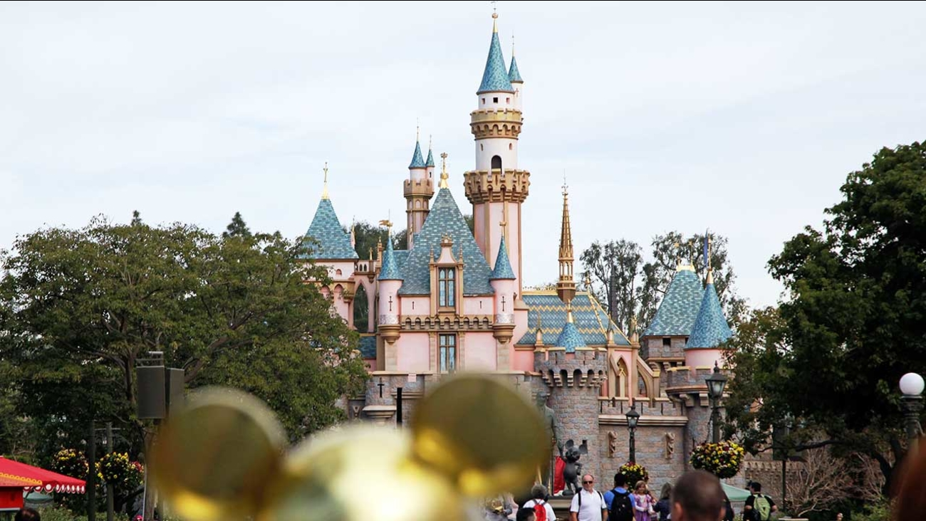 In this Jan. 22, 2015 file photo, visitors walk toward the Sleeping Beauty's Castle in the background at Disneyland Resort in Anaheim, Calif.