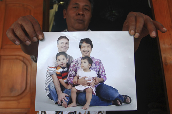 """<div class=""""meta image-caption""""><div class=""""origin-logo origin-image """"><span></span></div><span class=""""caption-text"""">Indonesian resident Widi Yuwono, the brother of Yuli Hastini, rear, holds a photograph of his sister's family who were on Malaysia Airlines Flight 17. (AP Photo)</span></div>"""