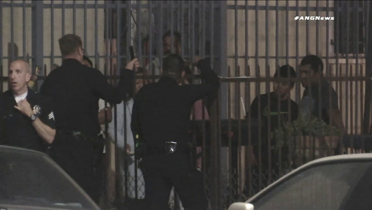 Los Angeles police speak with family members in South L.A. after an officer shot and wounded a pet dog that allegedly bit another officer.