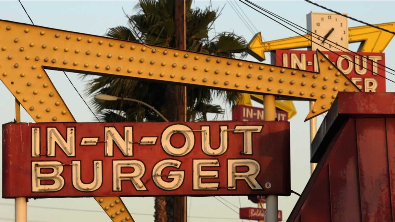 In this June 8, 2010 photo, In-N-Out Burger signs, two in the foreground from the fast food chain's original location in Baldwin Park, Calif.