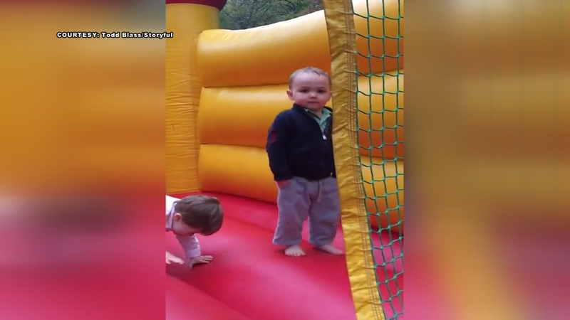 Toddler nonchalantly bounces in inflated bounce house