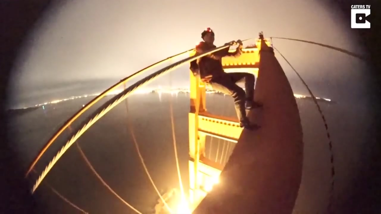 This undated image shows a daredevil climbing up the Golden Gate Bridge in San Francisco.