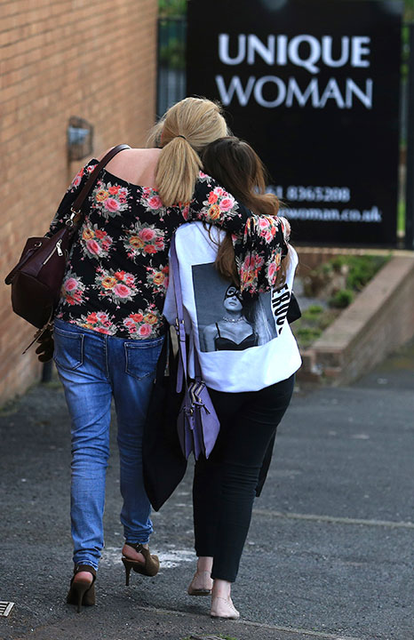 <div class='meta'><div class='origin-logo' data-origin='none'></div><span class='caption-text' data-credit='Rui Vieira/AP Photo'>A fan is comforted as she leaves the Park Inn hotel in central Manchester, England, Tuesday May 23, 2017.</span></div>