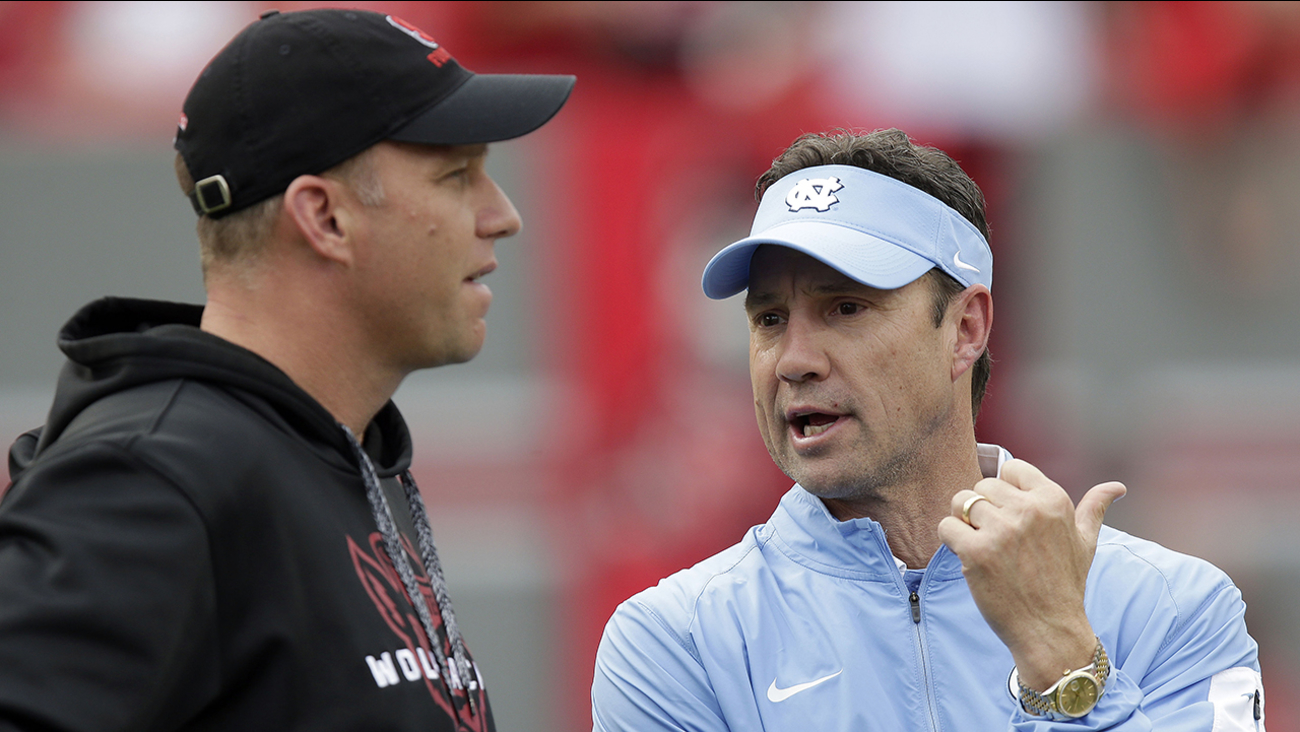 NC State coach Dave Doeren, left, and UNC coach Larry Fedora chat in 2015.