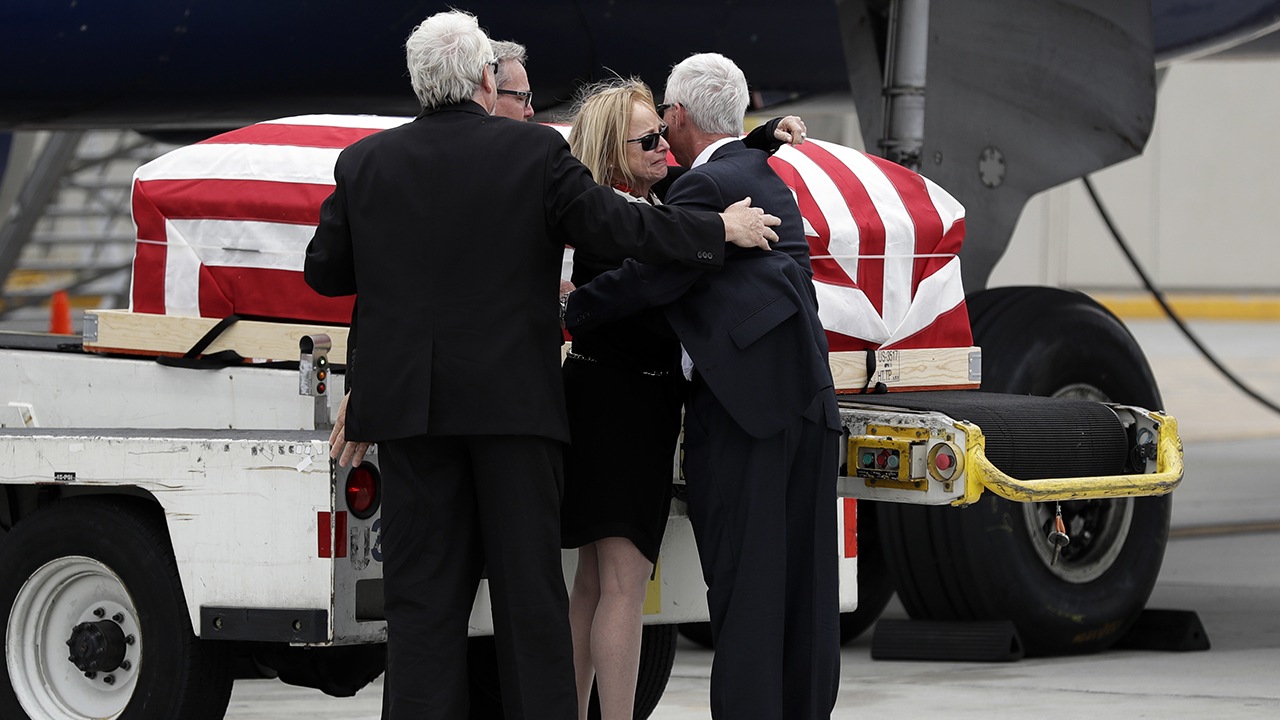 Deborah Crosby, center right, hugs her brother John Crosby, right, in front of her father's casket after its arrival to the airport Friday, May 26, 2017, in San Diego.
