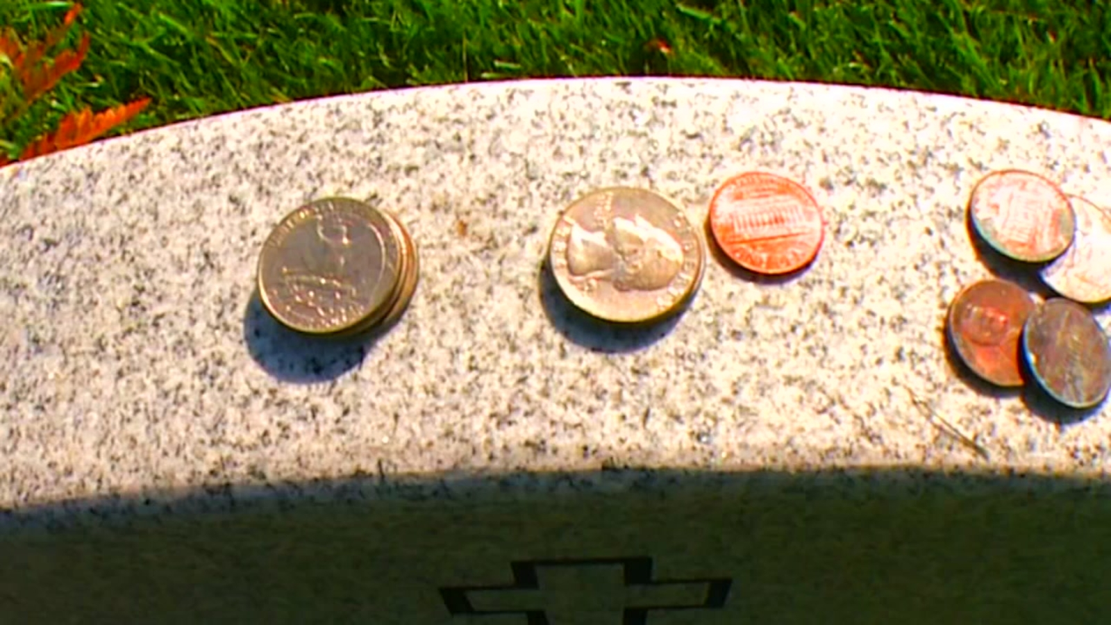 What do coins on military tombstones mean?