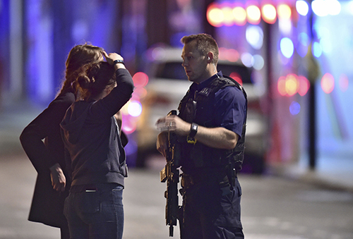 <div class='meta'><div class='origin-logo' data-origin='AP'></div><span class='caption-text' data-credit='Dominic Lipinski/PA via AP'>An armed Policeman talks to members of the public outside London Bridge Hospital as police are dealing with an incident on London Bridge in London, Saturday, June 3, 2017.</span></div>