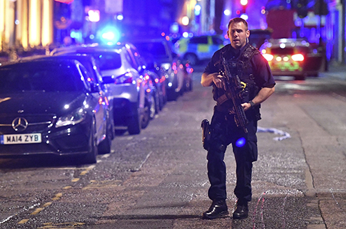 <div class='meta'><div class='origin-logo' data-origin='AP'></div><span class='caption-text' data-credit='Dominic Lipinski/PA via AP'>An armed police stands on Borough High Street as police are dealing with an incident on London Bridge in London, Saturday, June 3, 2017.</span></div>