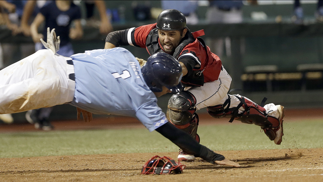 Davidson catcher Jake Sidwell tags out North Carolina's Brandon Riley at home plate Sunday in the ninth inning in Chapel Hill.