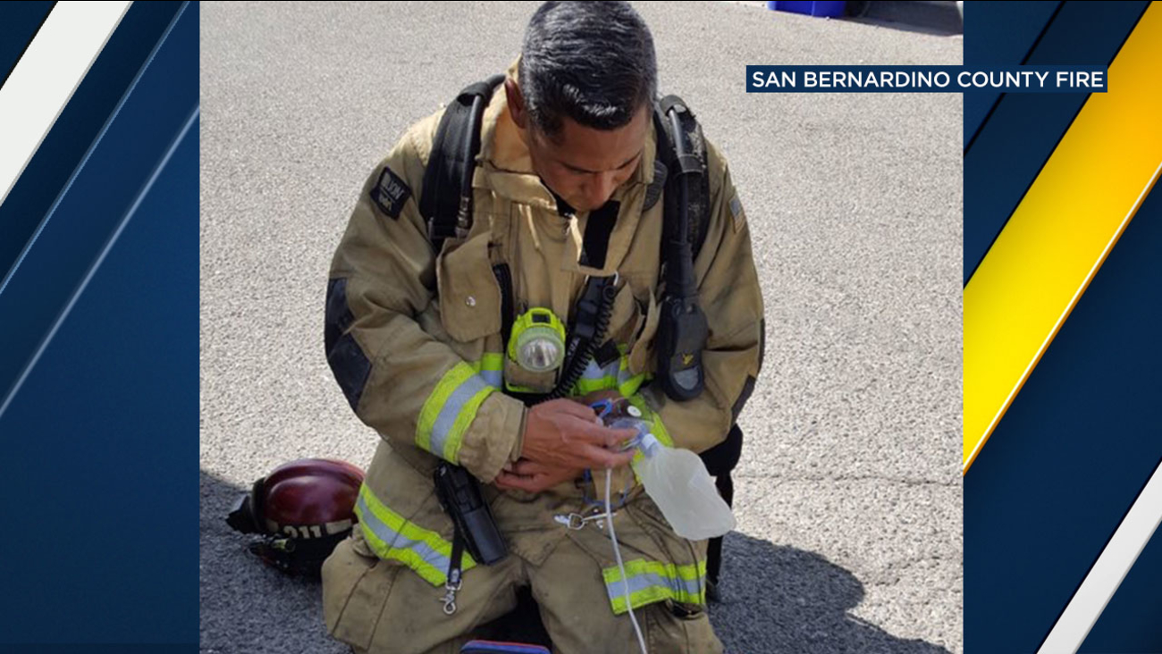 A San Bernardino County firefighter cradles a small puppy that was rescued from a burning home in Adelanto Tuesday.