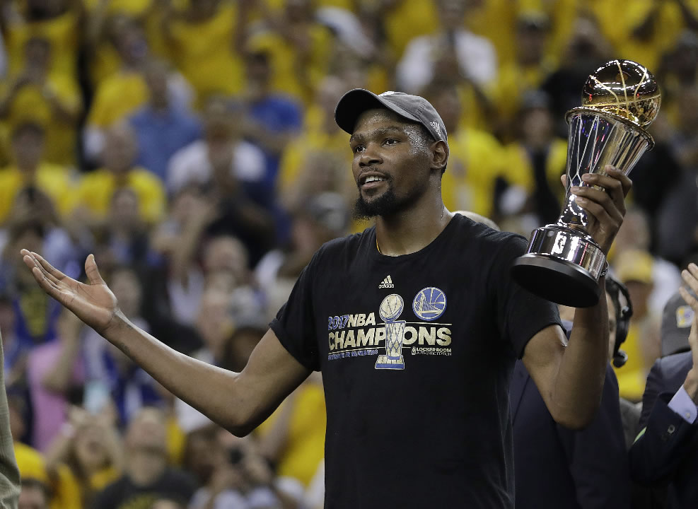 <div class='meta'><div class='origin-logo' data-origin='none'></div><span class='caption-text' data-credit='AP Photo/Marcio Jose Sanchez'>Warriors' Kevin Durant gestures as he holds the Bill Russell NBA Finals Most Valuable Player Award after Game 5 of basketball's NBA Finals in Oakland, Calif., Monday, June 12, 2017</span></div>
