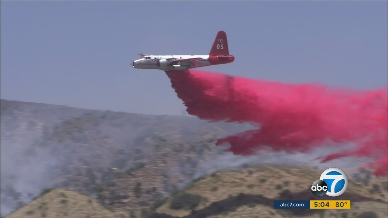 An airplane drops fire retardant on a brush fire in Banning on Thursday, June 15, 2017.