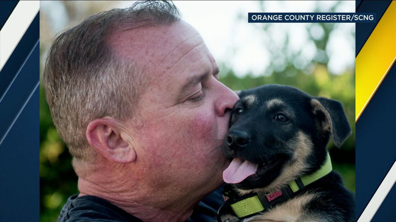 Sgt. Dave McGill kisses his new puppy Gordo.