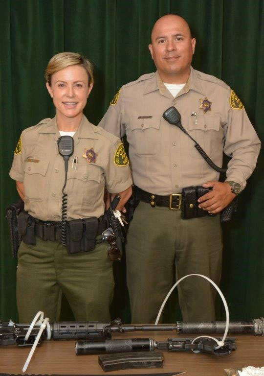 Deputies Katherine Zubo and Juan Gonzalez-Valencia are shown in front of the weapons they found after arresting a suspect at a Metro station.