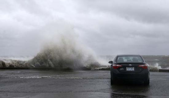 <div class='meta'><div class='origin-logo' data-origin='AP'></div><span class='caption-text' data-credit='Gerald Herbert'>People sit in a car and watch the waves on the shore of Lake Pontchartrain as weather from Tropical Storm Cindy, in the Gulf of Mexico, impacts the region in New Orleans.</span></div>