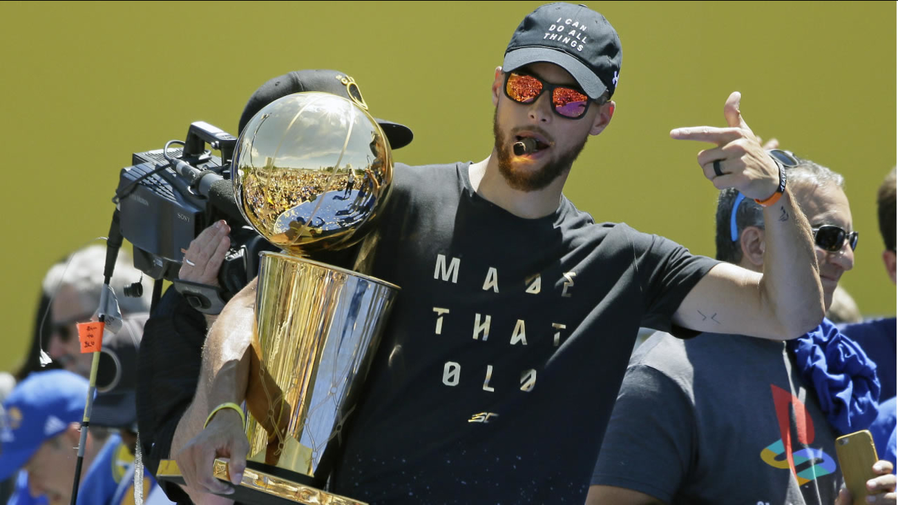 Stephen Curry points to the Larry O'Brien trophy during the Golden State Warriors NBA championship rally Thursday, June 15, 2017, in Oakland, Calif. (AP Photo/Eric Risberg)