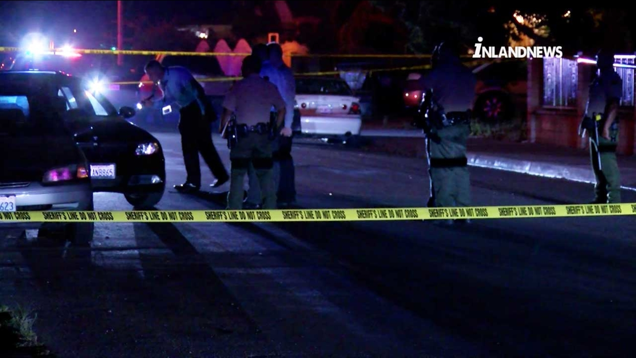 Law enforcement officials investigate the scene of a fatal shooting at an intersection in Fontana on Wednesday, June 28, 2017.