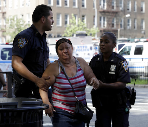 <div class='meta'><div class='origin-logo' data-origin='none'></div><span class='caption-text' data-credit='AP Photo/Julio Cortez'>A woman is escorted by officers near the Bronx Lebanon Hospital in New York after a gunman opened fire there on Friday, June 30, 2017.</span></div>