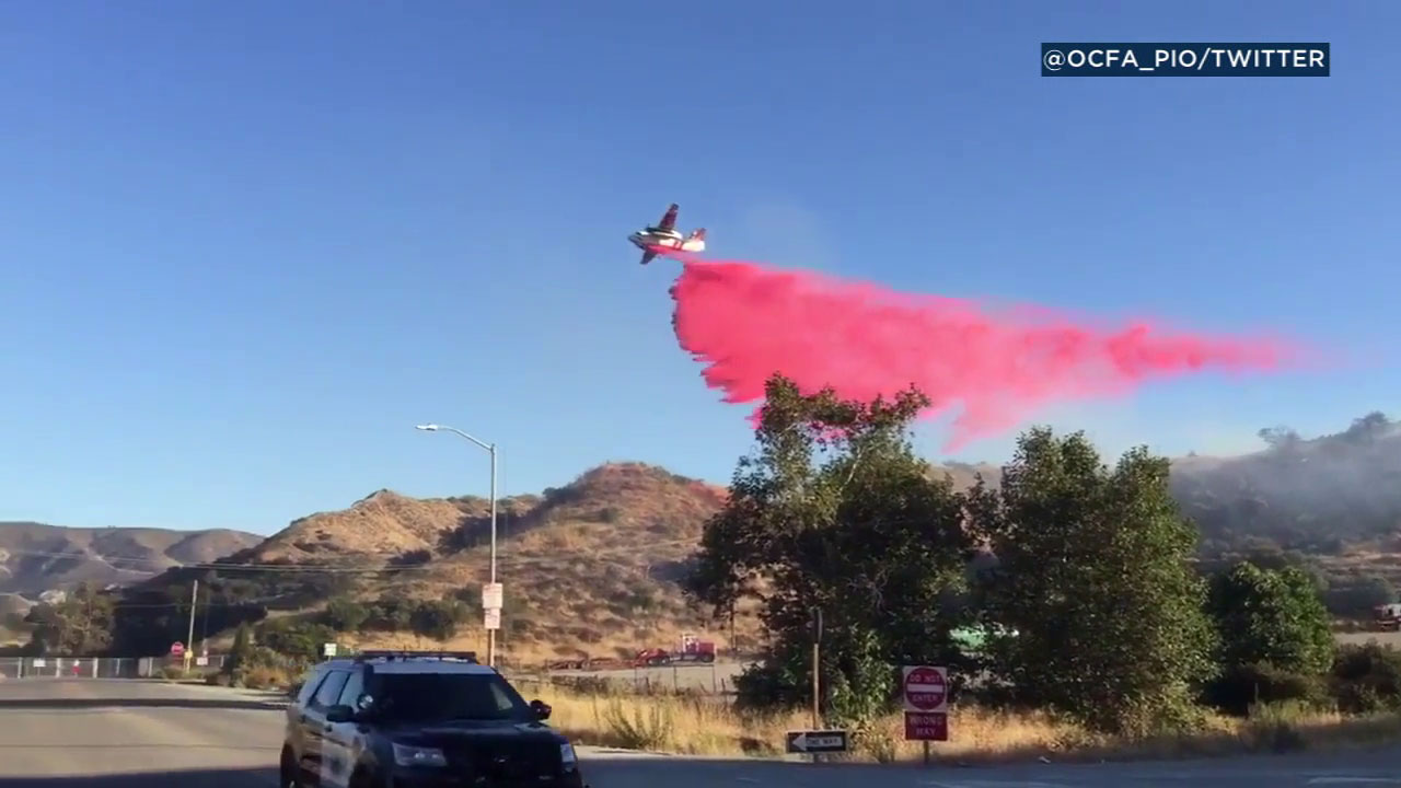An air tanker drops retardant on a brush fire along the 91 Freeway in Orange County on Monday, July 3, 2017.