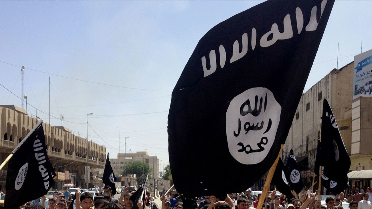 FILE - In this June 16, 2014 file photo, demonstrators chant pro-Islamic State group, slogans as they carry the group's flags.