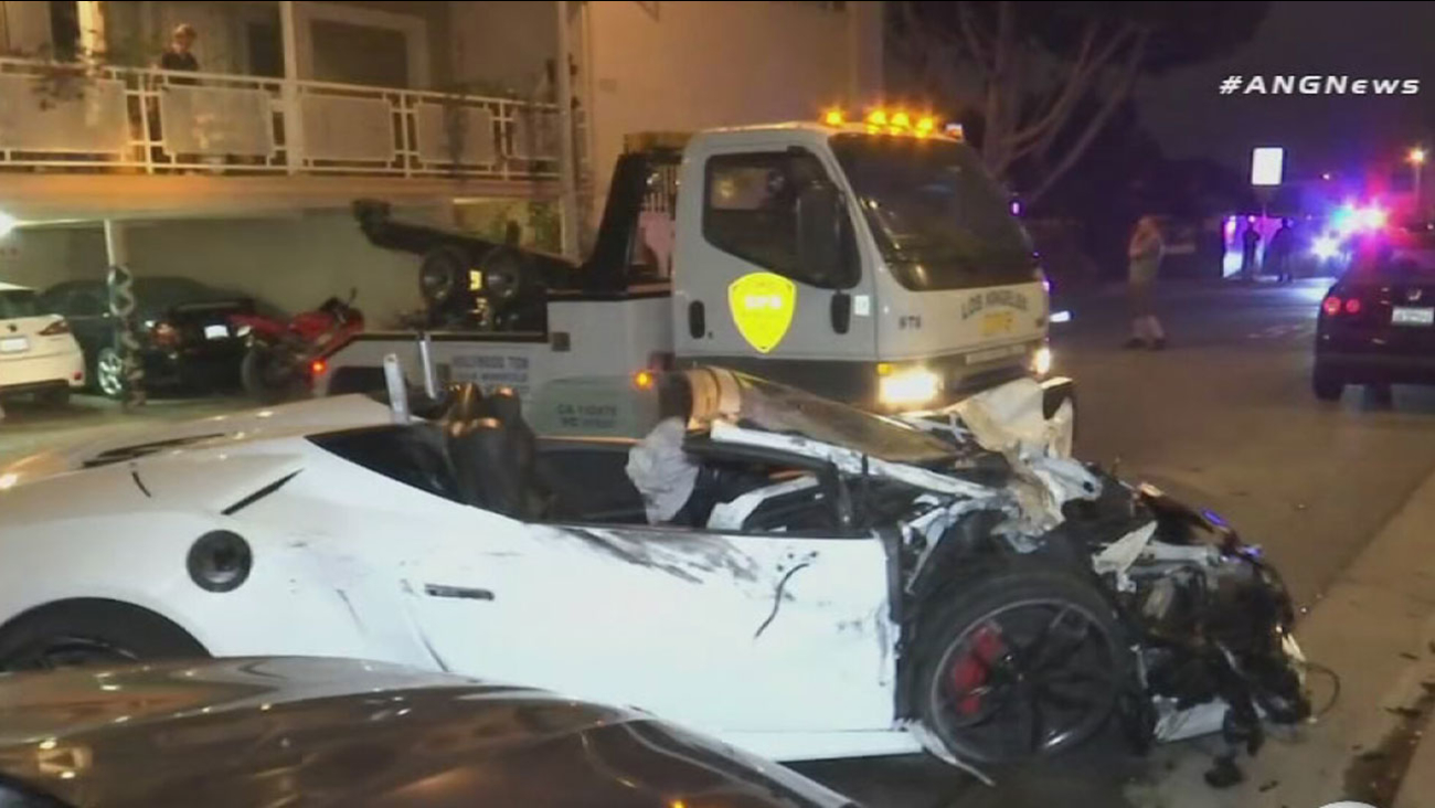 A smashed Lamborghini Huracan Spyder is shown being towed away after it was found damaged and abandoned when the driver allegedly crashed into parked cars in West Hollywood.