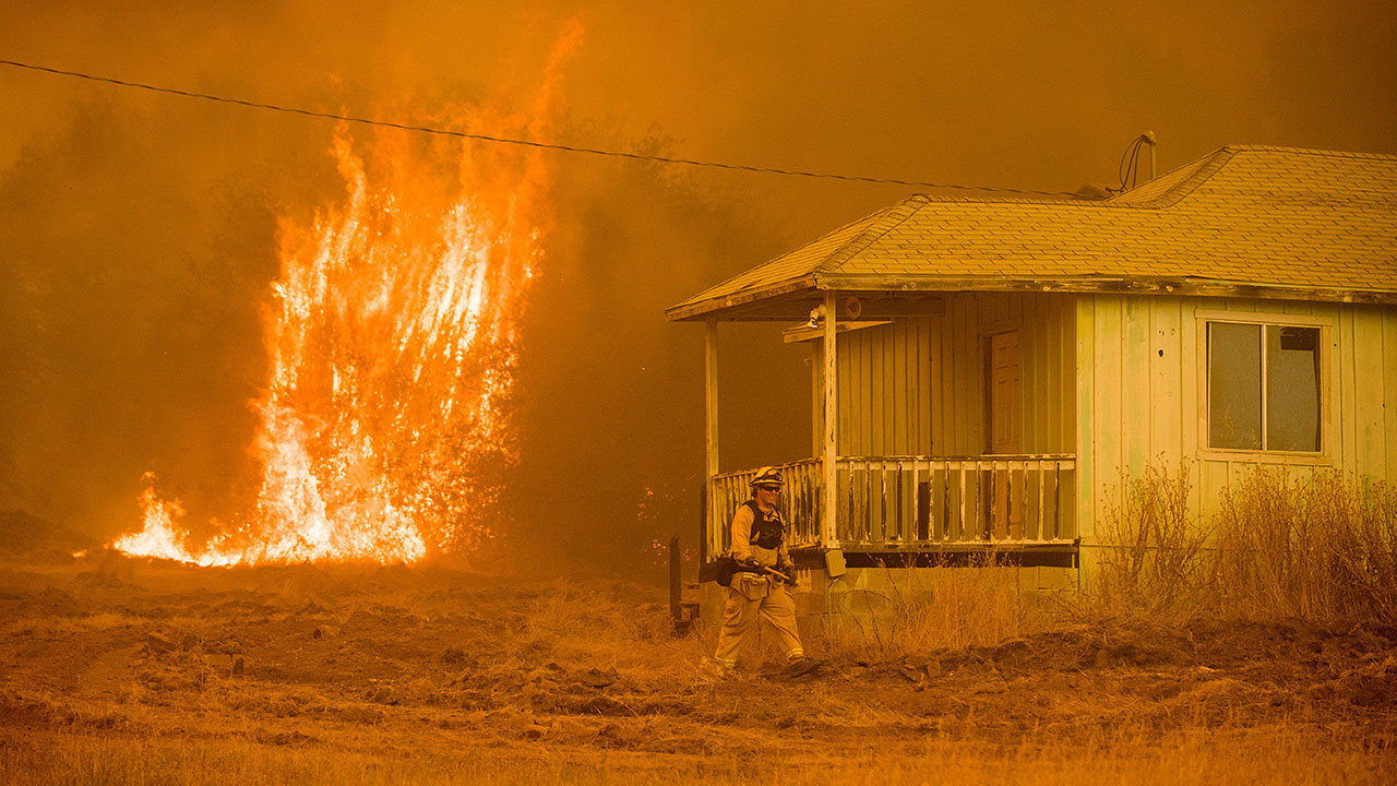 Flames rise behind a vacant house as a firefighter works to halt the Detwiler wildfire near Mariposa, Calif., on Wednesday, July 19, 2017.