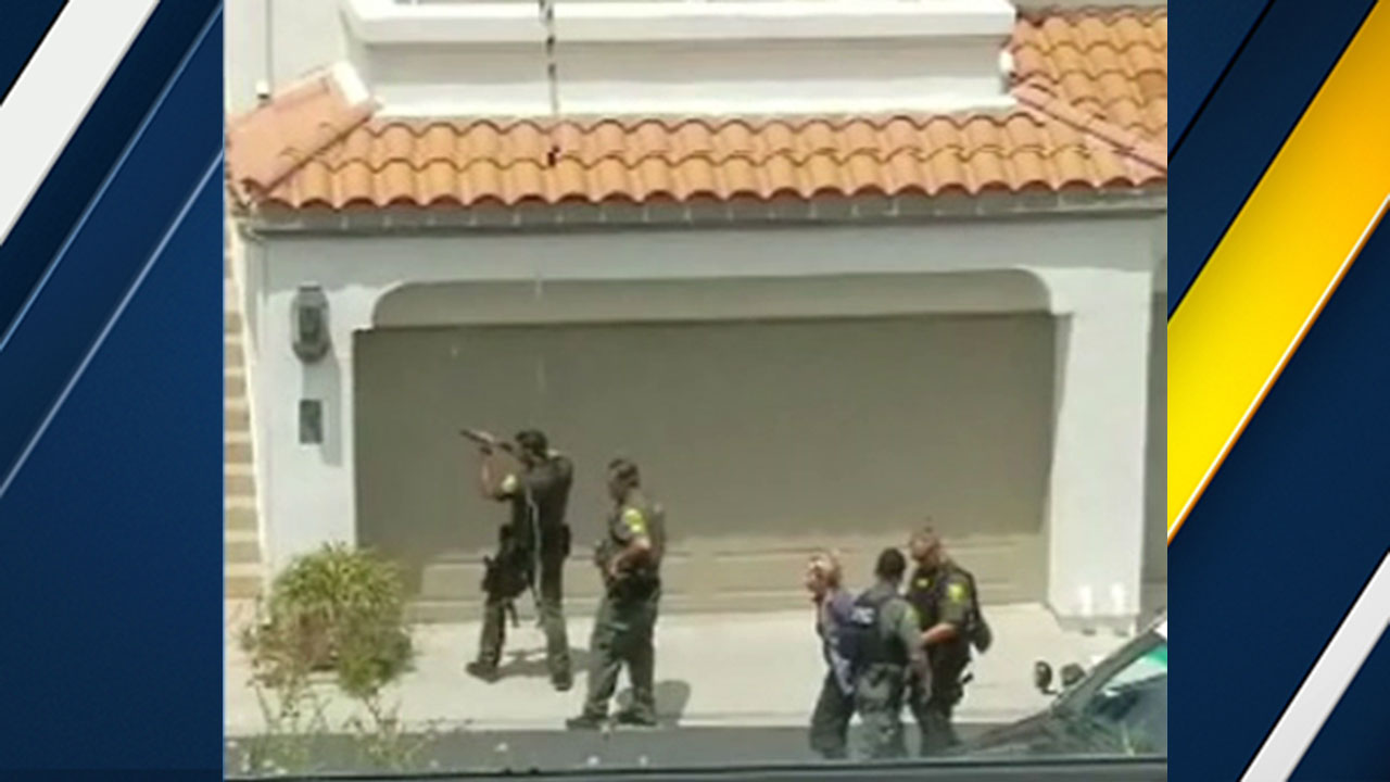 Orange County sheriff's deputies assist a woman who left a home in Dana Point where a gunshot was reported.