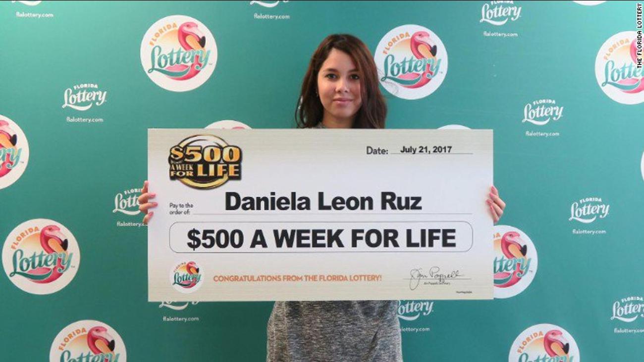 Daniela Leon Ruz of Orlando holding a check for $500 a week for life.